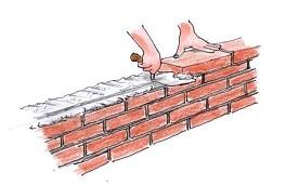 mano che costruisce un muro di mattoni